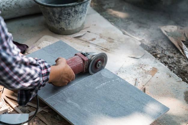Worker using electric circular saw cutting granite tile in construction site