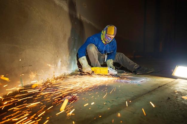 タンク内の溶接機金属炭素鋼部品底板に電動ホイールスパーク研削を使用する作業員