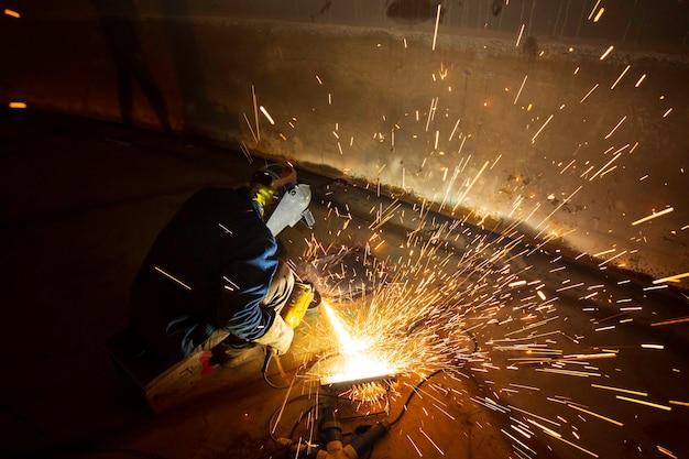Рабочий, использующий электроискровое шлифование на сварочной машине, металлической детали из углеродистой стали, нижней пластине внутри замкнутого пространства резервуара