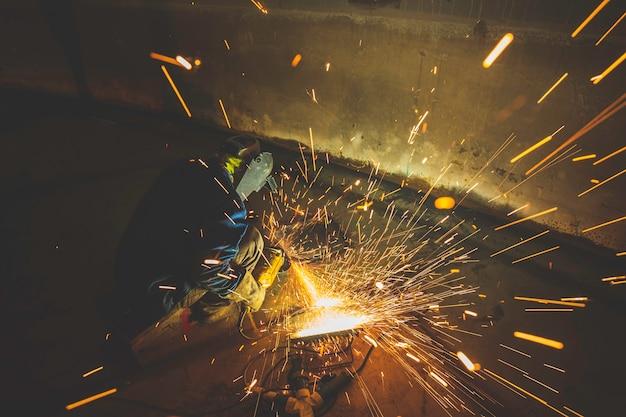 Рабочий, использующий электроискровое шлифование на нижней пластине детали сварщика из углеродистой стали, в замкнутом пространстве резервуара