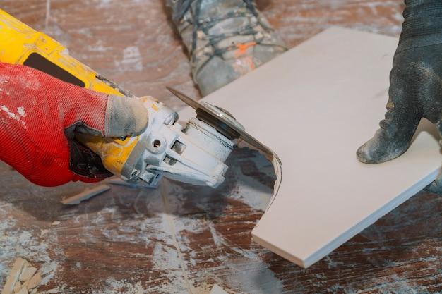 Работник, используя точильщика инструмент для резки плитки с пылью в фоновом режиме.