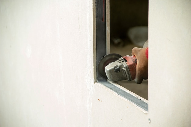 Worker using machine angle grinders at window edge cement board.