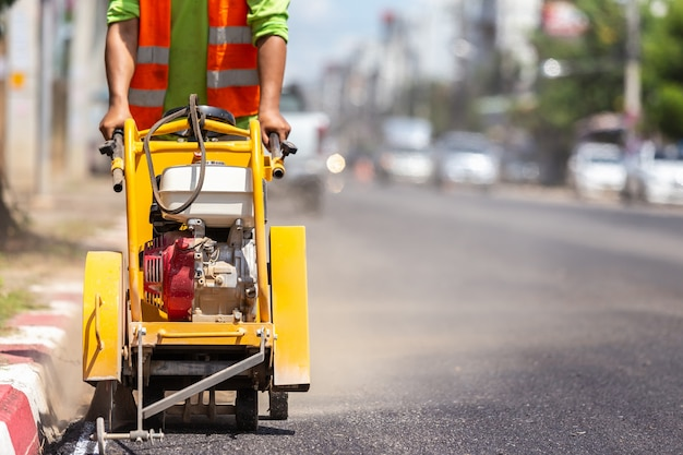 Worker using machine to cut the asphalt road