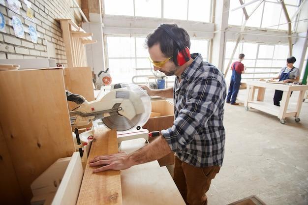 Рабочий с помощью станков на деревообрабатывающей фабрике