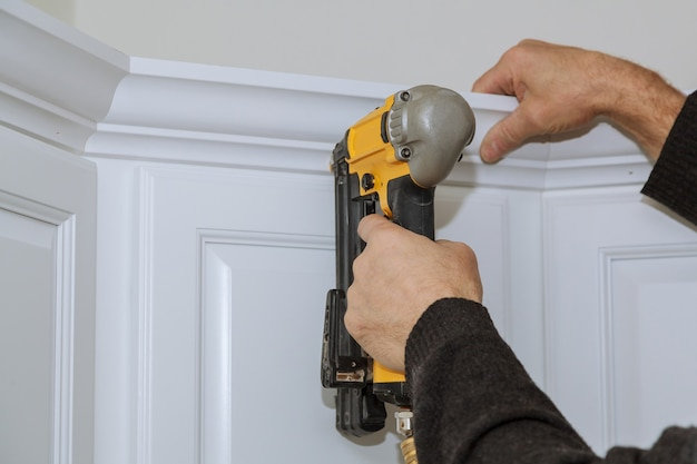 Worker using portable air gun nail in the nailing to crown moldings on new kitchen