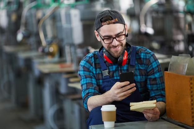 Работник, используя смартфон на перерыв