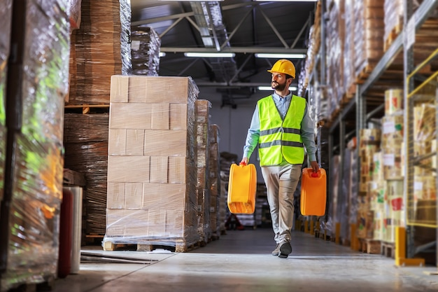 Worker in vest relocating cans with oil while walking in warehouse.