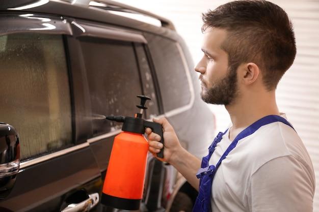 着色箔を適用する前に車の窓を洗う労働者
