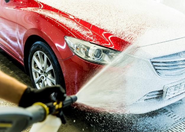 Рабочий моет машину с активной пеной на автомойке.