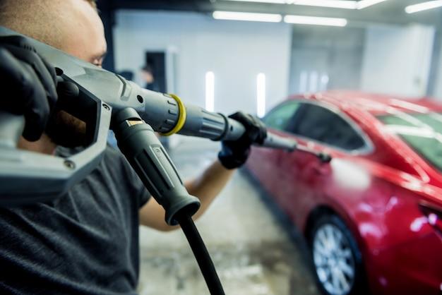 Рабочий моет машину водой под высоким давлением на автомойке.