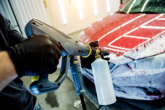 Worker washing car with high pressure water at a car wash.