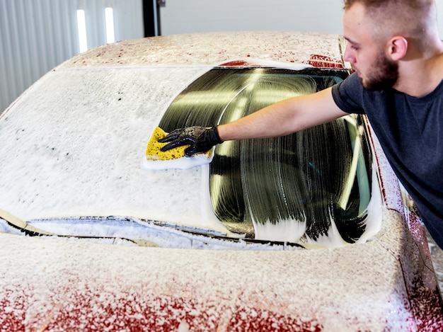 Worker washing red car with sponge on a car wash.