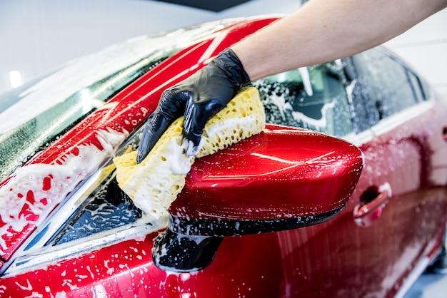 Рабочий, моющий красный автомобиль с губкой на автомойке