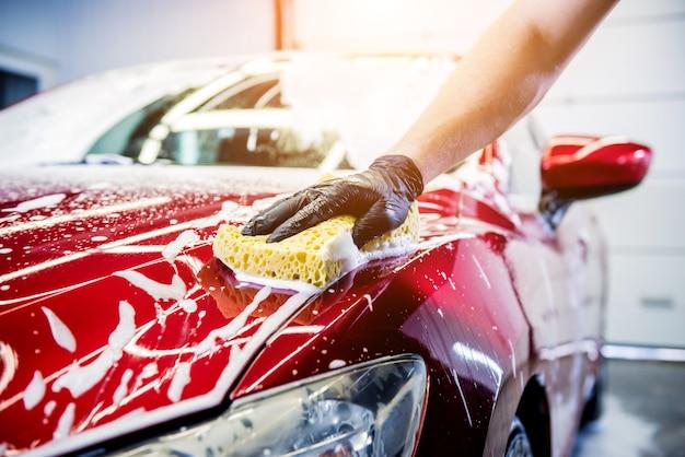 Рабочий моет красный автомобиль губкой на автомойке.