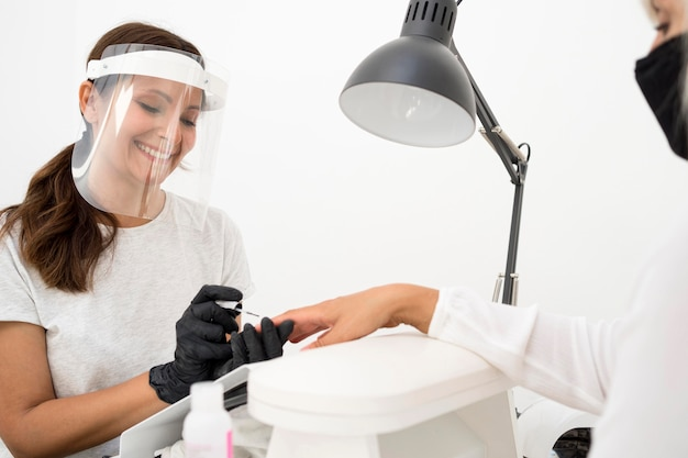 Worker wearing face shield and smiles at nail salon