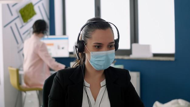 医療用フェイスマスクとヘッドフォンを着用して、ビジネスプロジェクトで働くマイクについてパートナーと話し合っている労働者。ウイルス病を予防するために社会的距離を保つ同僚