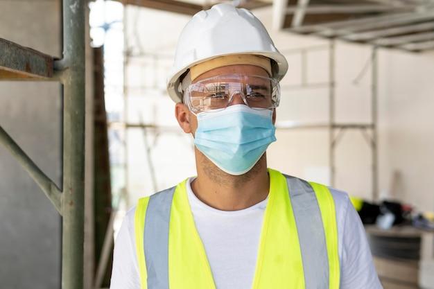 Рабочий в медицинской маске на строительной площадке