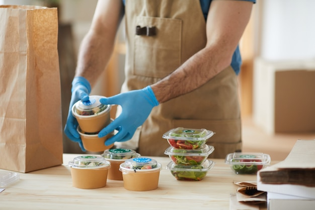 Worker wearing protective gloves packaging orders at wooden table in food delivery service