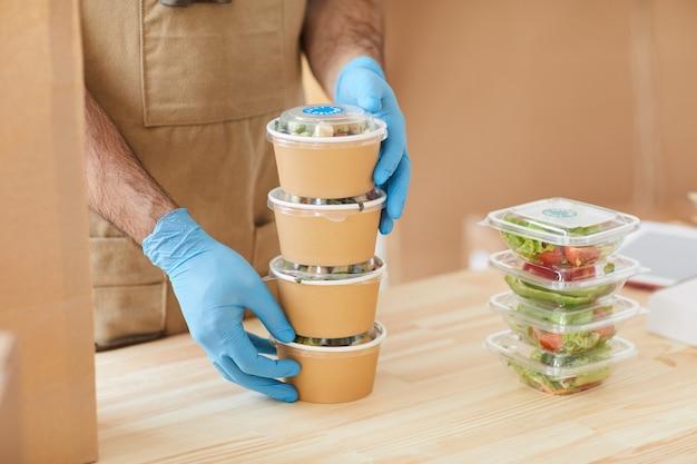 Работник в защитных перчатках безопасно упаковывает заказы за деревянным столом в службу доставки еды