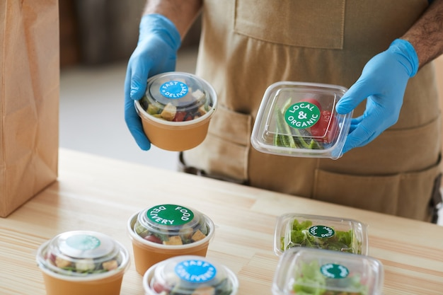 Worker wearing protective gloves safely packaging orders at wooden table in food delivery service