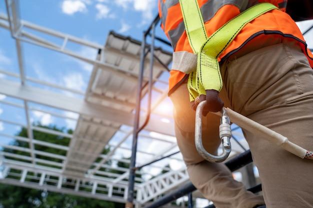 건설 현장에서 높은 곳에서 작업하는 안전 장비와 안전 벨트를 착용한 작업자.