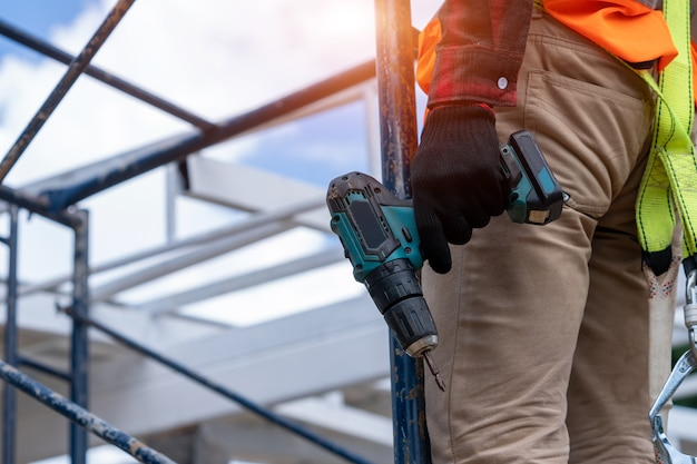 Worker wearing safety equipment and safety belts working on height at construction site.
