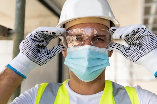 Рабочий в защитных очках на строительной площадке