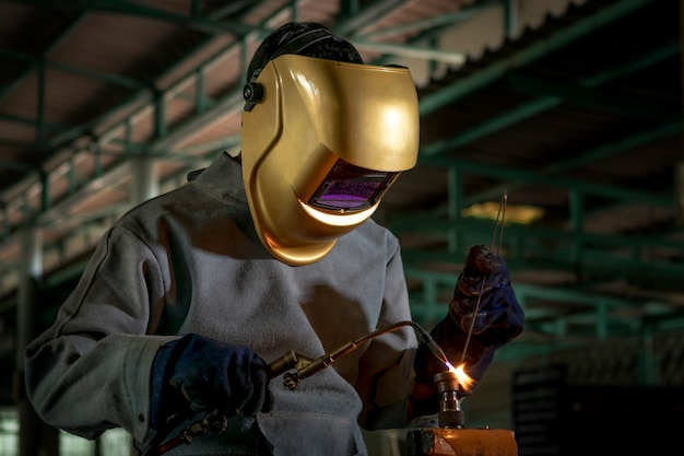 Worker welder working welding gas steel in industry with safety mask gloves and safety equipment.