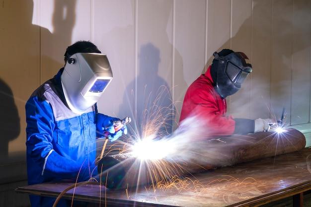 Рабочий сваривая часть стали в промышленной мастерской
