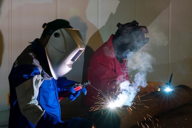 工業用ワークショップで鋼の一部を溶接する労働者