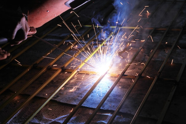 Worker welding and bright sparks