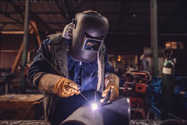 労働者の溶接鉄。保護スーツとマスク。ワークショップのインテリア。