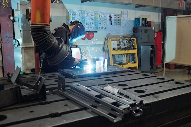 Worker in welding mask using torch while welding metal part in dark industrial shop