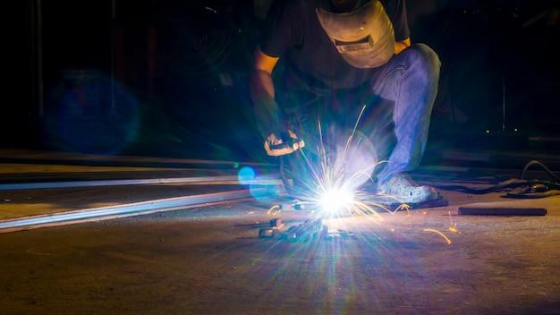 作業者の溶接金属、低光の鋭い火花のフラッシュ光線に焦点を当てる