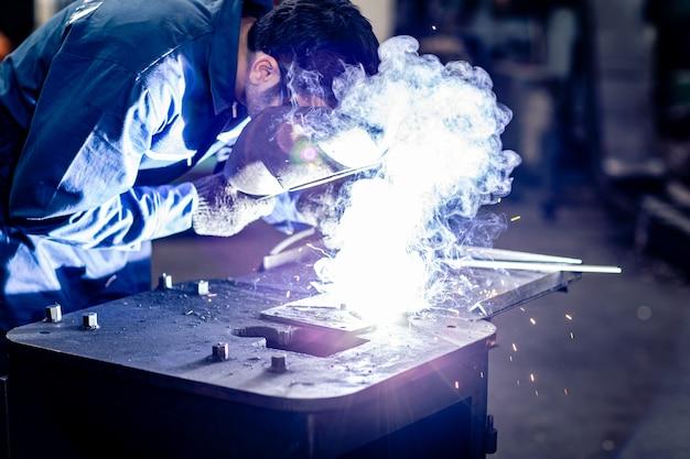 鋼の重工業の製造で働く金属を溶接する労働者。