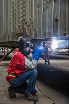Работник сваривая стальную часть вручную в порте