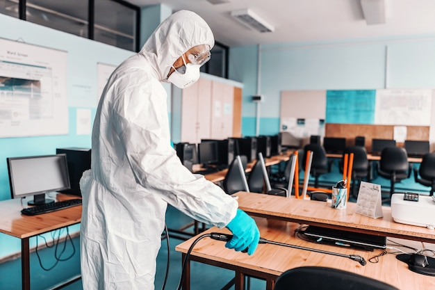 Worker in white sterile uniform, with rubber gloves and mask on holding sprayer