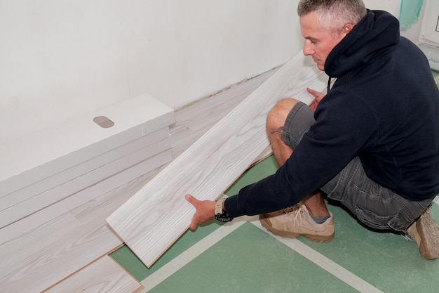 A worker who connects the laminate flooring during the renovation of the house.