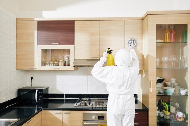 労働者はキッチンキャビネットを拭く