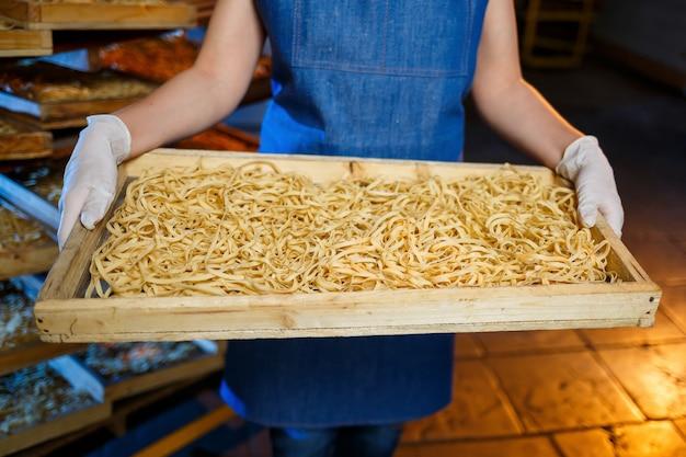 パスタの箱を持った労働者。女の子はスパゲッティの生産に取り組んでいます。麺作り。パスタ工場。