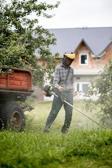 그의 손에 가스 깎는 기계와 노동자, 집 앞에서 잔디를 깎고. 남자의 손에 트리머. 잔디를 절단하는 정원사. 생활 양식.