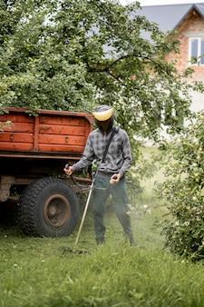 그의 손에 가스 깎는 기계와 노동자, 집 앞에서 잔디를 깎고. 남자의 손에 트리머.