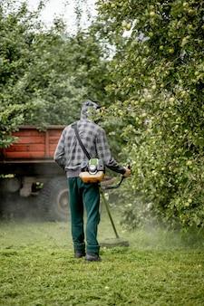 Рабочий с газовой косилкой в руках косит траву перед домом