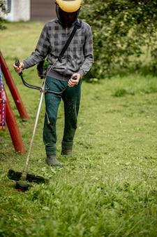 그의 손에 가스 깎는 기계를 가진 노동자, 집 앞에서 잔디를 깎고