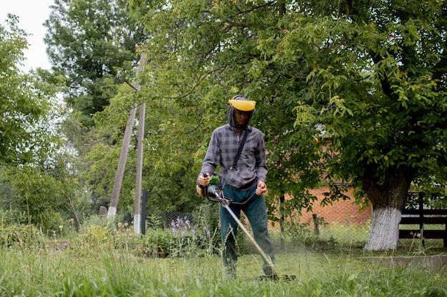 그의 손에 가스 깎는 기계와 노동자, 집 앞에서 잔디를 깎고.