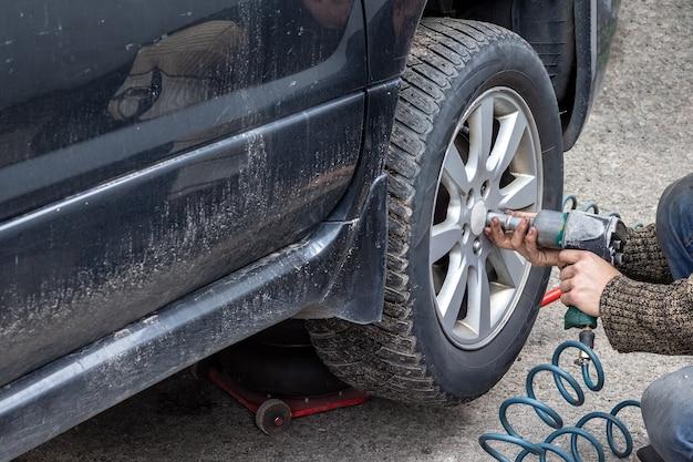 Рабочий с пневматическим ключом откручивает болты от колеса автомобиля