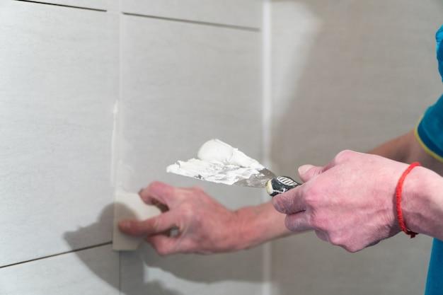 Рабочий резиновым шпателем заполняет швы раствором технология укладки плитки.