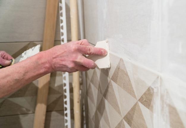 ゴムヘラを持った労働者が縫い目を溶液で満たすタイルを敷設する技術