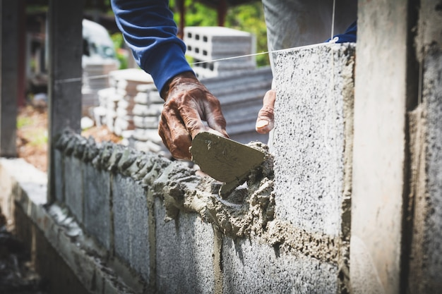Worker with block concrete cement mortar wall at construction site.