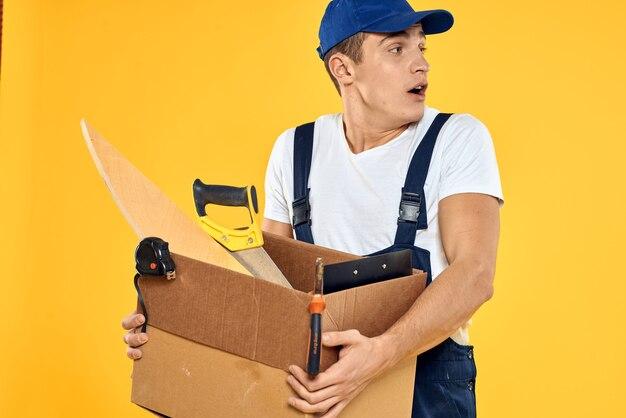 手工具ローダー黄色の背景にボックスを持つ労働者。高品質の写真